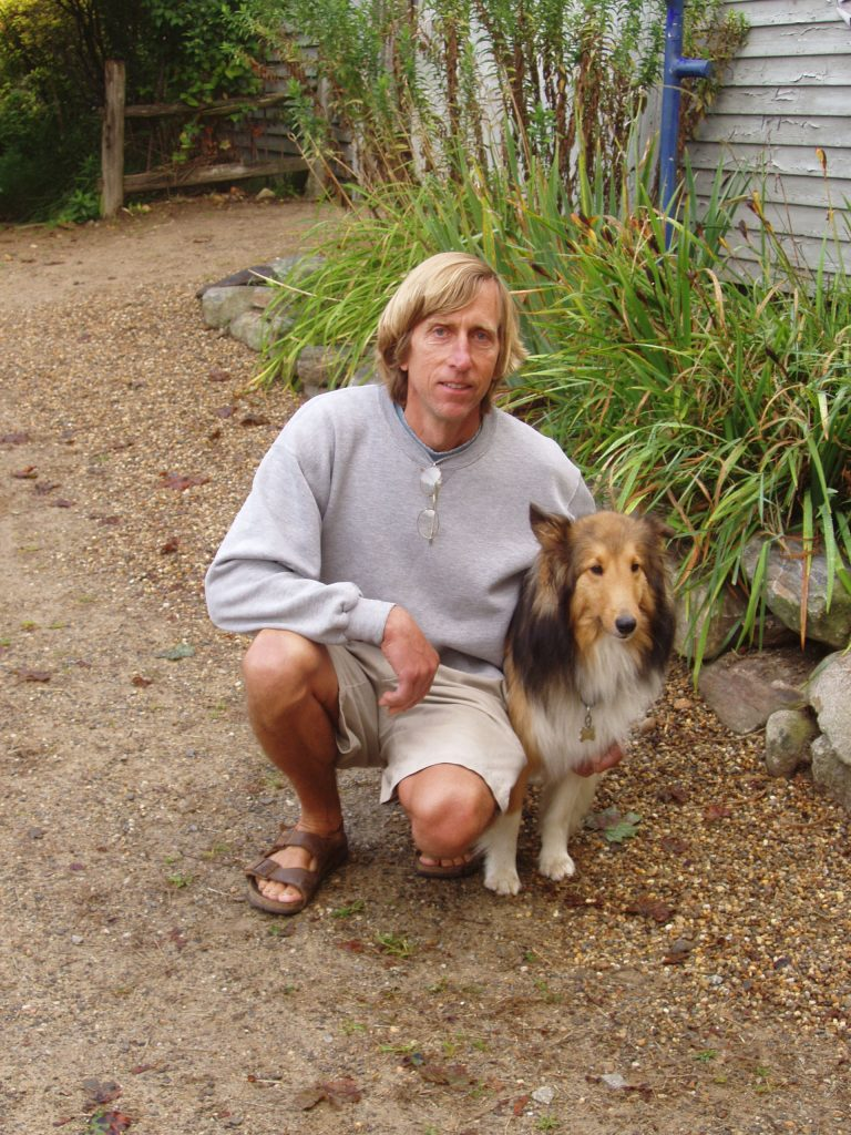 Don Williams and pet sheltie posing in the garden.